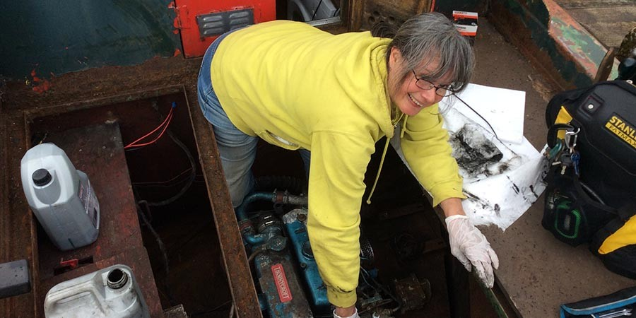 A lady carrying out maintenance on a boat engine