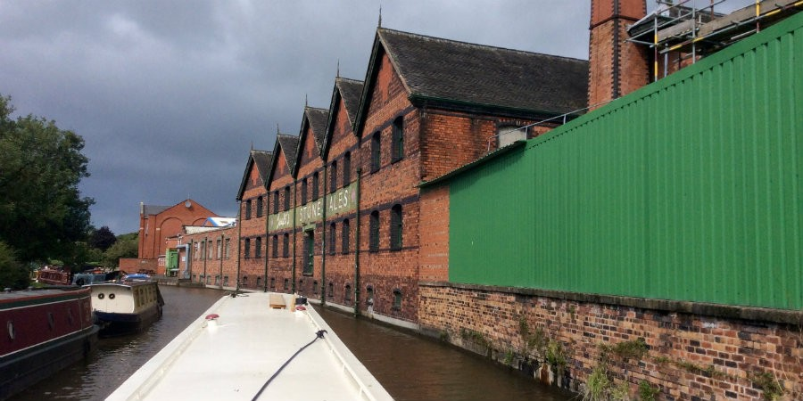 A narrowboat cruises past the brewery in Stone