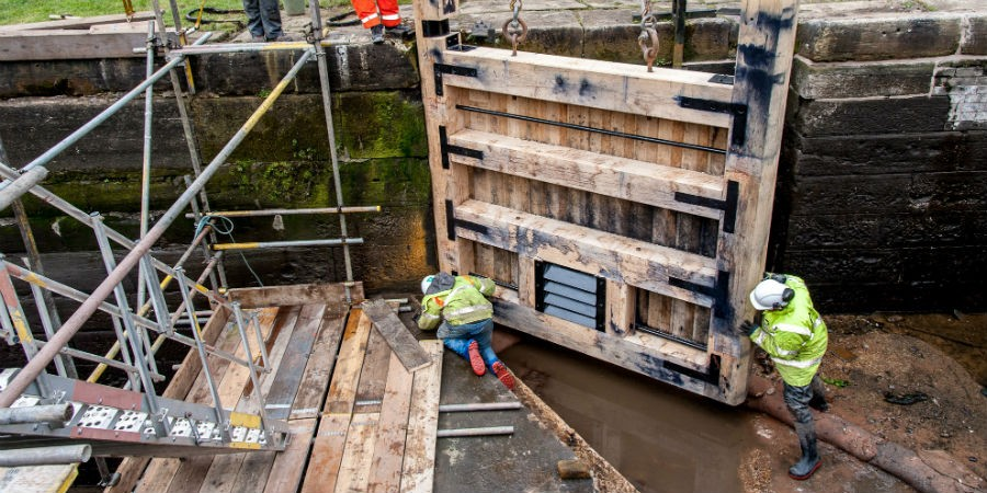 workers tending to new lock gate in drained canal