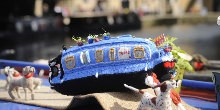 A knitted narrowboat sitting on top of a real narrowboat