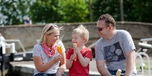 A family eating ice cream by the canal