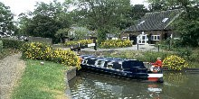 Boat entering lock on Stratford on Avon Canal, lock-keeper cottage nearby