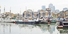 Boats moored in basin with London Docklands in background