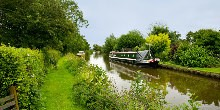 Boats moored along grassy towpath of canal