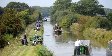 Anglers on towpath of canal with boats passing by