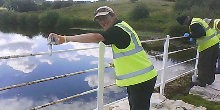 Robert Bullock, Towpath Taskforce volunteer, painting metal railings on bridge with white paint