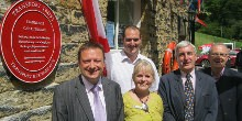 Group of colleagues stood by Red Wheel plaque at Standedge Tunnel