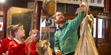Explorer education volunteer with pupils using pulleys to lift sacks in Gloucester Waterways Museum