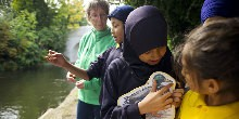 Explorer education volunteer with pupils on towpath with duck picture