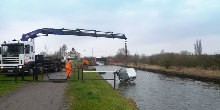 A crane pulling a car out of the canal
