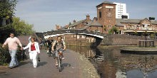 Walkers and cyclists on towpath by bridge over canal in Birmingham
