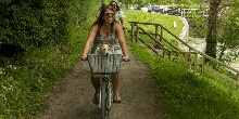 Women riding their bikes on the towpath with locks in background