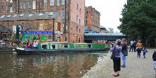Narrowboat on the water with passersby taking photos