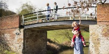Family walking under a beam bridge