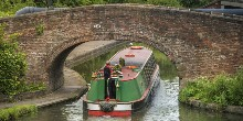 Narrowboat travelling under an arch bridge