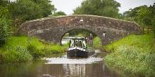 A canal boat going under a bridge