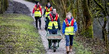 Youth volunteer group in the north west walking along a path with wheelbarrows