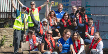 Group shot of young volunteers cheering by the canal in Leeds