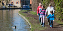 Adults and children walking along towpath