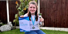 Izzy Gibbins with junior championships trophy and certificate 2020