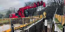 Crane lifting new gate into canal