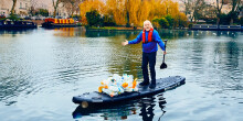 Comedian Bill Bailey collecting plastic with a paddleboard on the water
