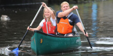 Father and daughter canoeing along the canal