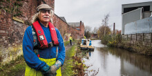 Portrait of a male volunteer standing next to a canal, wearing hi-viz clothing, life-vest and blue sweatshirt with flat cap and sunglasses